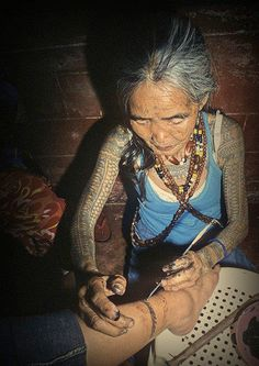 Elder performing traditional tattoo..