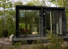 An art studio in the woods made of two steel shipping containers in Amagansett, New York.