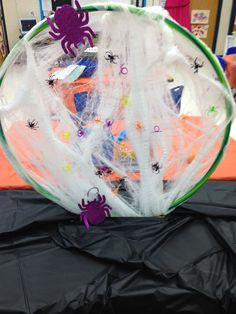 Preschool Halloween spider toss. We wrapped a hula hoop with dollar store bought cob webs and then simply masking taped it to the top of a table. Students then tried from different distances to throw plastic spiders into the web.