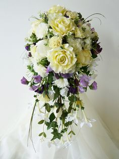 Lucinda - A very pretty shower bouquet designed for an English Country garden theme featuring soft lemon roses, ivory and lemon carnations, peony buds, lilac and purple sweetpeas, hydrangea and a stephanotis trail.