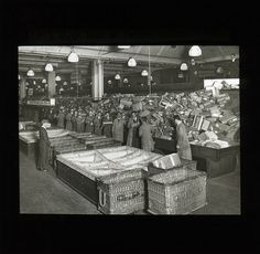 A black and white photographic lantern slide of room with a large wooden trough along one wall which is filled with parcels. The parcels arrive via a chute in the top right hand corner. A group of men stand next to the trough and there are large boxes divided into sections and wicker baskets to the left hand side. Date: c.1930-c.1940.