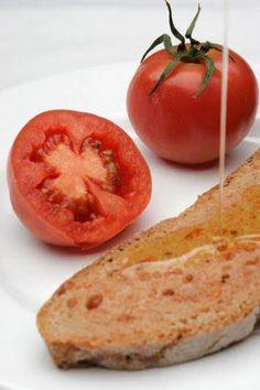 Pa amb tomàquet.Abrir un tomate maduro,restregarlo en una rebanada de pan rústico(no lo tritureis,frotarlo) y regar con aceite de oliva virgen.Receta catalana sencilla y deliciosa.Bon profit!.