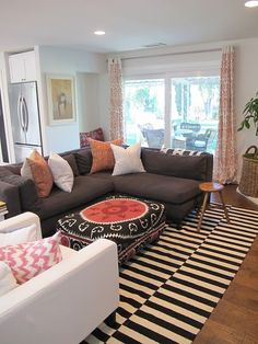 I love the contrast between the striped rug and patterned ottoman.
