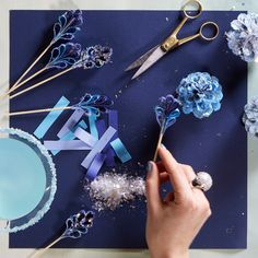 Stir things up with these wintery drink garnish- es. Take strips of different blue hue paper and dab them with glue and glitter. Then fold in half and glue them to a wooden stirrer.