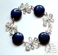 Beautiful rich blue Lapis Lazuli flat disc beads linked with silver plated copper wire flowers.    This is a large bracelet.  Length: 9 inches. £20.00
