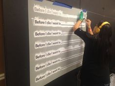 """In the run-up to TED2012, TED Senior Fellow Candy Chang installs her interactive community art project Before I Die outside the Creativity Lab social space, painstakingly daubing stencils with white paint. """"No spray paint allowed in here,"""" she says. """"So I'm doing it the Zen way!"""" Photo: Jason Wishnow"""