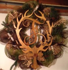 Extra large wreath made with a variety of neutral tone colors of deco mesh and fibers, accented with sprigs of evergreen, pinecones, rolled birch bark, raffia, burlap, twine, etc. The centerpiece is made of wood which sports an initial and majestic antlers. A wood cross has been added towards the bottom of the wreath. Antler Wreath, Deco Mesh Crafts, Wood Crosses, Birch Bark, Neutral Tones, Made Of Wood, How To Make Wreaths, Xmas, Christmas