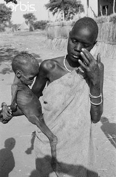 A mother and her child in a feeding center in Sudan. This picture was taken by Kevin Carter.  -----I wanna make this stop.