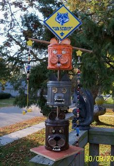 Cub scout totem pole made from recycling plastic coffee cans, apple sauce/dessert cup containers, and buttons for eyes.