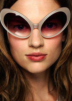 Anteojos estilo ojo de gato, combinan cristales tornasolados en vinotinto con la montura en acrílico y gris. Su gran tamaño contribuye a proteger el rostro de los rayos ultravioleta