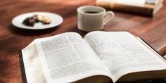Uma Bíblia aberta ao lado de uma xícara de café