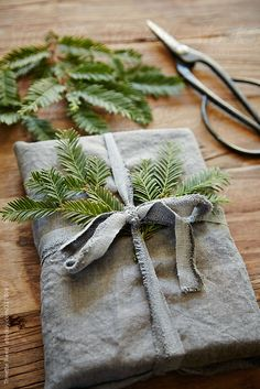 Still life of homemade linen wrapped present with pine branch by Trinette Reed