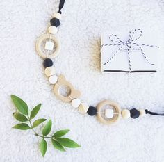 A modern eco friendly Pram String. Made from a mix of wooden rings, beads & silcone beads both round & geometric with a bear shaped teether...