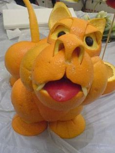 This orange cartoonish tiger or cat is a great example of Food Art made with oranges and apples