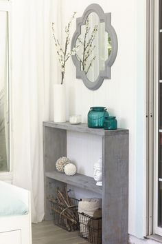 Simple grey shelving with a grey framed mirror and turquoise and white accents