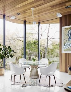 Cover Story: This House in Austin Has a Tree Growing Right Through It - Photo 5 of 10 - Because the property slopes to the rear, the home's eastern view is of treetops right outside. In the dining nook, Executive Armchairs by Eero Saarinen join a Warren Platner table beneath a Serge Mouille ceiling light. A patterned rug by AVO rests on the terrazzo tile floor.