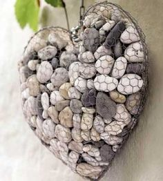 A Piece of discarded Chicken wire, and a few collected pebbles! I think this would be pretty inside or out. I think it would a;lsao be attractive with the 'frame' sprayed a Flat Black for extra contrast. - Wire and Stone Heart - Beautify your yard or garden with this decorative DIY home decor craft project made from wire and pebbles. Kids are always giving me rocks..great place to put them