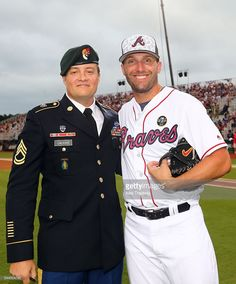 Sgt. 1st Class Corey M. Calkins and Jeff Francoeur #18 of the Atlanta Braves after throwing out the ceremonial first pitch prior to the game between the Miami Marlins and the Atlanta Braves at Fort Bragg Stadium on Sunday, July 3, 2016 in Fort Bragg, North Carolina.