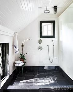 walk-in shower.  Large tile base is colored, with white walls...