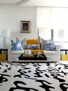 Toile pillows with La Fiorintina and a solid, contrasting throw, a sculpted black and white rug, cutout lamps, and a vignette on the invisible coffee table.  Very effective. By Caitlin Wilson.