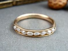 Delicate fresh water pearls are cradled in the folds of this solid 14k gold ring. The stones are held securely in place by a sterling wire. This ring