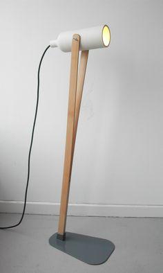 Esta luminaria de pie llamada Jump, cuenta con un cilindro regulable de cerámica y un sencillo soporte con dos piezas de madera de arce so...