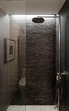 Pebble flooring is paired with stacked stone walls makes you feel like you are showering in nature! exposed piping running up the wall to the showerhead is really great look. lighting up at the ceiling, gives you great light in the shower.