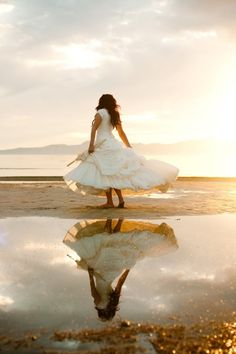 bride shot- dress twirl on the beach reflection in the water around sunset.