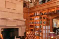 Library design in the Country French manor style, with a large fireplace and floor to ceiling built in bookshelves. Discovered on www.Porch.com
