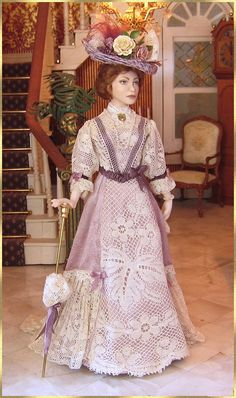 She is wearing a gorgeous dress made of lilac silk and off white lace.