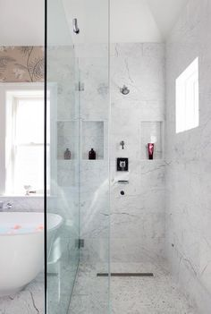 Beautifully designed seamless glass shower is fitted with carrera marble hexagon floor tiles and a marble surround tiles framing tiled his and her shower niches positioned on either side of a polished nickel shower kit as natural light streams in from a square window on an adjacent wall.