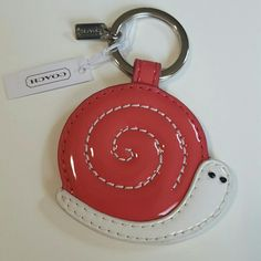 Coach Snail Keychain fob This is a beautiful Coach keychain fob that is brand new with tags. This is a lovely pink shelled snail with a swirl sewn into it with a white body and two little black beaded eyes. This is brand new with tags and in perfect condition.  F66278 Coach Accessories Key & Card Holders
