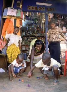 In Sefwi Wiawso, Ghana, Jewish children and their mothers play dreidel in front of a general store owned by a member of the House of Israel community. photo/bryan schwartz