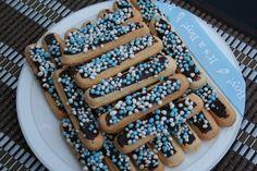 Lange vingers met chocoladeglazuur en blauw-witte muisjes op een bord, versierd met een lint 'it's a boy'