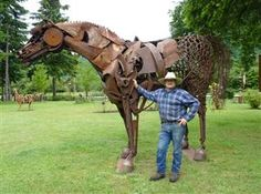 Artist Dan Klennert, a former mechanic, lets visitors meander through his outdoor sculpture park. The artist stands with 'Cleopatra,' a horse sculpture made from scrap metal.
