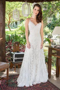 O modelo de renda com pouco volume e decote nas costas, arrematado com uma flor no cabelo, é uma inspiração para noivas modernas.