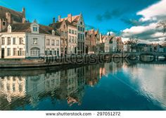 Scenic city view of Bruges canal Spiegelrei with beautiful medieval houses, their reflections and Bridge Carmersbrug, Belgium. Toning in cool tones