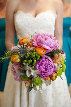 The bouquets will be similar in shape and texture to the one pictured with white anemones, blue thistles, orange astilbe, ivory peonies, yellow billy balls and ivory hydrangeas, blue forget-me-nots, and seeded eucalyptus wrapped in ribbon