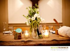 Rustic themed wedding reception table setting and centerpiece. White and green flowers in mason jars. www.kevintrimmer.com