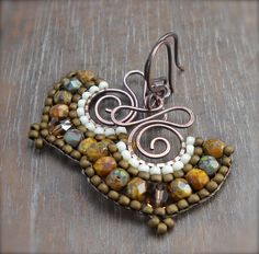 These rustic earrings have been handcrafted from copper wire and earthy green, brown, and ivory colored japanese seed and Czech glass beads have been woven into a fan shape along the edges. MEMBER - Heidi Lee Design