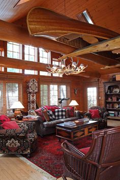 dirondack décor includes leather, wicker, bold fabrics and the chandelier (made from naturally shed antlers). Note the diamond motif in the blanket chest and grandfather clock. #greatroom #cabin #rustic