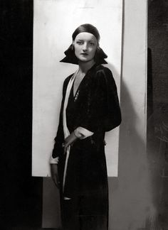 ca. 1929 — Jule Andre wearing black satin turban with draped fabric that forms triangular 'wings' at back and sides, designed by Agnes; and black satin dress with white angular cuffs and lapel.