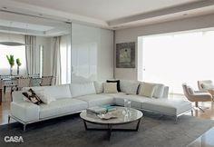 Apesar de básico,o sofá em L da Flexform (Casual Móveis) contém uma aura de descontração, já que uma extremidade funciona como banco sem braço nem encosto. Portas de correr de vidro branco (Cinex) ampliam a luminosidade, na sala de estar criada por Marco Aurélio Viterbo.