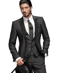 Three piece charcoal gray suit. Black/white satin skull tie with matching handkerchief, metallic pocket chain for waistcoat, skull tie clip, skull cufflinks and skull pendant with crystal rhinestones. White fashion shirt and simple cuff with double buttonhole for cufflinks, black leather belt with ON gothic buckle, black skull hat and black cane with skull handle with rhinestones.