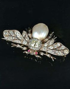 A pearl and diamond bee brooch, circa 1890, the wings and body set with cushion-shaped, old brilliant and rose-cut diamonds, the largest stone at the centre, with a baroque pearl abdomen and cabochon ruby eyes, pearl untested, detachable brooch fitting, may be mounted as the centrepiece of an associated cultured pearl necklace (not illustrated), width 5.0cm.