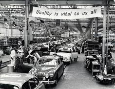 """Jaguar Cars, Browns Lane, Coventry, production line. The banner above the track reads """"Quality is vital to us all"""" 18th October 1961"""