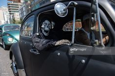 A man takes a skeleton doll in his Volkswagen Beetle, also known as Fusca, during a parade to celebrate the Brazilian national day of the Fusca, along Ipanema beach in Rio de Janeiro on January 20, 2015. AFP PHOTO / YASUYOSHI CHIBA