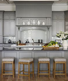 """As the hub of the home, the kitchen gets pretty busy. One way to keep the scene calm is to ground the entire space in shades of gray. To keep the overall look inviting and warm, opt for seating in natural textures such as wood or bamboo over slick chrome. Tip: If you're considering painting your kitchen cabinets yourself, be sure to go with a latex satin finish for easy cleaning. See more interior design ideas on """"Gray Rooms We're Loving Right Now"""" on the One Kings Lane Style Guide!"""