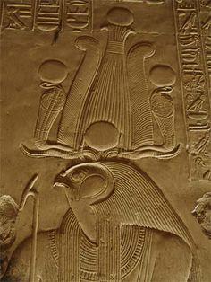 Divinité hiéracocéphale (peut être Horus) portant la couronne Hemhem, une des couronnes rituelles de l'Égypte antique, formée de trois couronnes Atef (couronne Hedjet surmontée de deux plumes d'autruches et parfois un disque solaire) qui surmontent des cornes de bélier plates - Bas-relief sur les murs d'un temple d'Abydos.