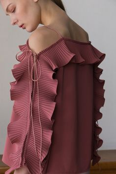 The Calin Top in Pink, featuring thin straps, square neckline, dimple sleeves in ruffle detailing with self-tie. Pull on. COMPOSITION AND CARE Dry clean only Please treat with care to extend the life